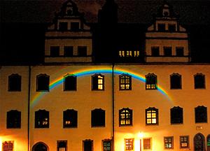 Lichtkunst am Historischen Rathaus der Lutherstadt Wittenberg: Das fließende Wasser des Stadtbaches spaltet das Licht in seine Spektralfarben, nach einem Gemälde von Lucas Cranach.